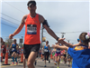 Male Runner with an orange shirt giving a child a high five at the 6 mile moment