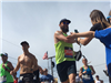 Runner with a beard and sunglasses smiles as he gives kids high fives with both hands