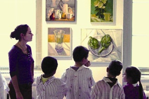view of several children and a teacher from the back viewing an art exhibit while wearing smocks