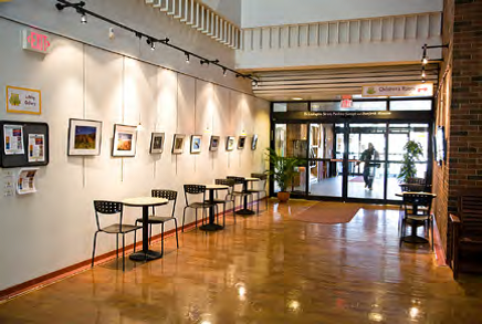 view of the interior lobby of library with cafe tables and artwork on the walls