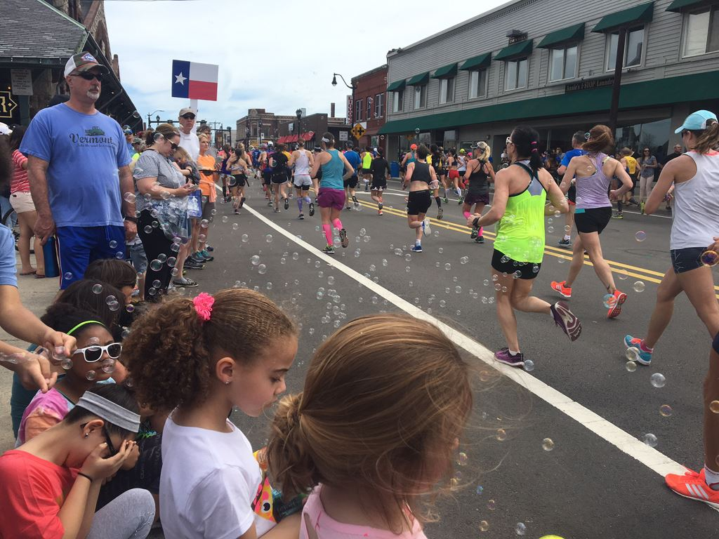 image of runners from the back and crowds facing them with bubbles floating around