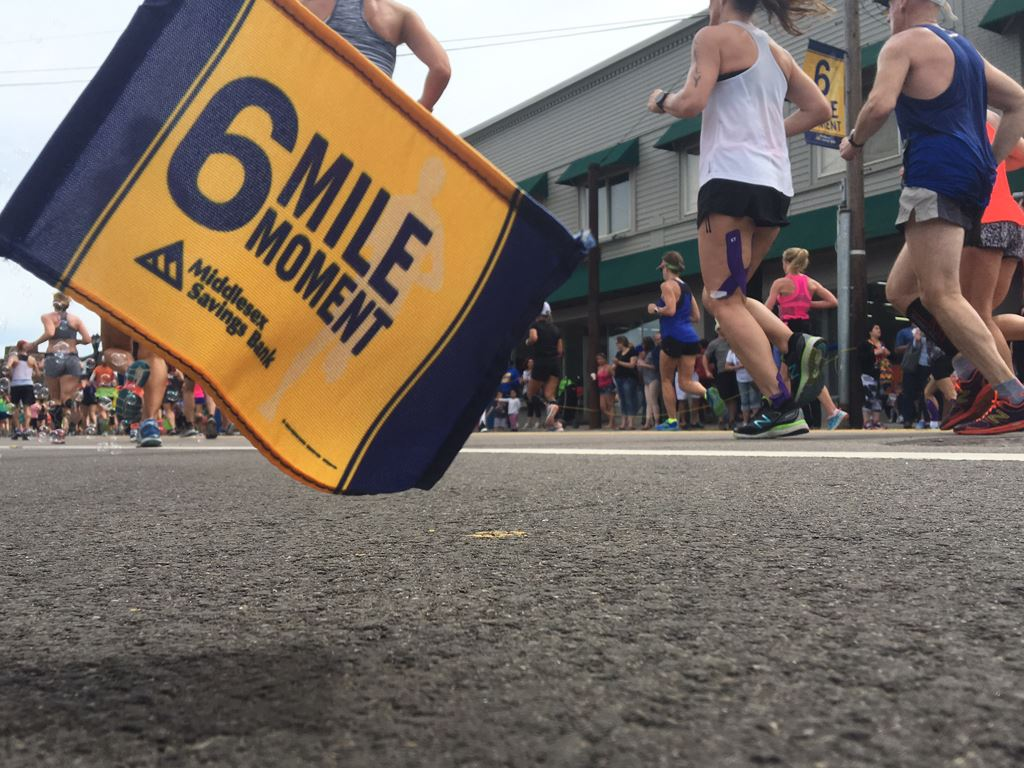 Image of 6 Mile Moment flag with runners and a building in the background from an angle at ground le